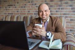 Lyckligt indiskt mansammanträde på kafét med anteckningsboken och bärbara datorn med koppen kaffe som ler se kameran Royaltyfri Foto