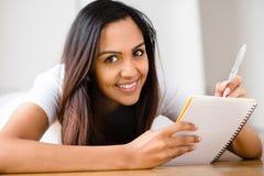 Lyckligt indiskt studera för handstil för kvinnadeltagareutbildning Arkivbild