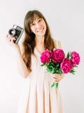 Lyckligt innehav för ung kvinna i handbukett av pioner och den gamla tappningkameran Sött romantiskt ögonblick le kvinna Royaltyfri Fotografi