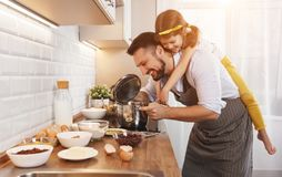 lyckligt kök för familj Fader- och barndottern knådar deg a arkivbild