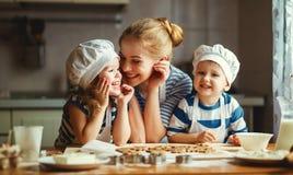 lyckligt kök för familj moder och barn som förbereder deg, lodisar arkivbilder