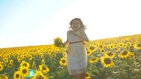 Lyckligt köra för liten flicka som är lyckligt fritt över fältet med solrosor ultrarapidvideo lukta på den stora solrosen arkivfilmer