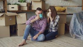 Lyckligt klinga för gift par rånar och att dricka te, medan sitta på golv i ny lägenhet efter inflyttning tillsammans arkivfilmer