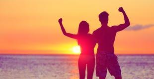 Lyckligt konditionfolk på stranden på att böja för solnedgång