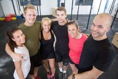 Lyckligt konditiongenomkörarelag på idrottshallen Royaltyfri Foto