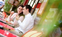 Lyckligt koppla ihop att äta läckra macaroons Royaltyfria Foton