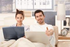 Lyckligt koppla ihop bläddra internet i säng hemma royaltyfri fotografi