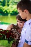 Lyckligt koppla ihop med en bukett av röda ro som kramar i en sommar parkerar Arkivbilder