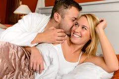 Lyckligt koppla ihop sängmanen som ger kysskvinnan arkivfoton