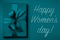 Lyckligt kort för kvinnadaghälsning med gåvaasken, band, pilbåge på mörk turkosbakgrund royaltyfri foto