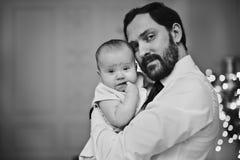 Lyckligt krama för fader som är hans, behandla som ett barn dottern för julgranljusen i bakgrunden fotografering för bildbyråer