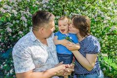 Lyckligt krama för mamma och för farsa behandla som ett barn parkerar in på solig dag för sommar royaltyfri fotografi