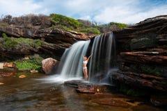 Lyckligt kvinnaanseende under en vattenfall i bushlandvildmark royaltyfri foto