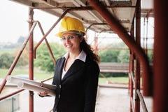Lyckligt kvinnaarbete som arkitekten In Construction Site fotografering för bildbyråer
