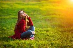 lyckligt kvinnabarn Den härliga kvinnlign med långt sunt hår som tycker om solljus parkerar in, sammanträde på grönt gräs Vår Royaltyfria Bilder