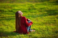 lyckligt kvinnabarn Den härliga kvinnlign med långt sunt hår som tycker om solljus parkerar in, sammanträde på grönt gräs Vår arkivbilder