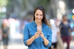 Lyckligt kvinnahandstilmeddelande i en smart telefon på gatan royaltyfria foton