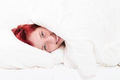 Lyckligt kvinnanederlag i säng Arkivbild
