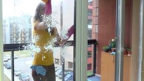Lyckligt kvinnarengöringfönster och leende arkivfilmer