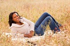 Lyckligt kvinnasammanträde i le för fält Royaltyfri Foto