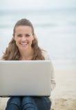 Lyckligt kvinnasammanträde med bärbara datorn på den kalla stranden Arkivfoto