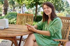 Lyckligt kvinnasammanträde på en tabell på terrassen Royaltyfri Foto
