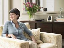 Lyckligt kvinnasammanträde på fåtöljen royaltyfria bilder