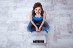 Lyckligt kvinnasammanträde på golvet med bärbara datorn Arkivbilder