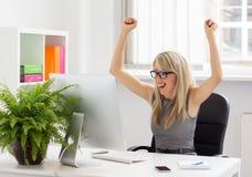 Lyckligt kvinnasammanträde på hennes skrivbord med armar upp Royaltyfri Foto