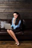 Lyckligt kvinnasammanträde på soffan och användabärbara datorn Arkivbilder