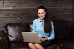 Lyckligt kvinnasammanträde på soffan och användabärbara datorn Royaltyfri Foto