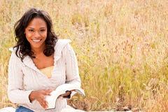 Lyckligt kvinnasammanträde utanför läsning Arkivfoton
