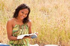 Lyckligt kvinnasammanträde utanför läsning Arkivbild
