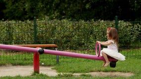 Lyckligt kvinnligt barn i den vita kjolen och skjortan som spelar på gungbrädet utanför under sommar Sunny Day arkivfilmer