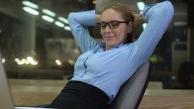 Lyckligt kvinnligt framstickande som kopplar av på kontorsstol som tillfredsställs med projektresultat, arbete stock video