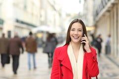 Lyckligt kvinnligt gå samtal på telefonen i gatan arkivfoton