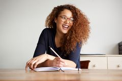 Lyckligt kvinnligt högskolestudentsammanträde på skrivbordhandstil i bok royaltyfri bild