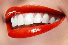 Lyckligt kvinnligt leende för närbild med sunda vita tänder, ljust rött kantsmink Cosmetology-, tandläkekonst- och skönhetomsorg Fotografering för Bildbyråer