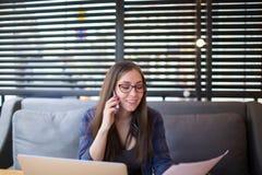 Lyckligt kvinnligt publikationsläsningavtal och ha celltelefonkonversation arkivfoto