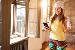 Lyckligt kvinnligt se på mobiltelefonen inomhus royaltyfri fotografi