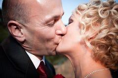 lyckligt kyssa för brudbrudgum Arkivbild