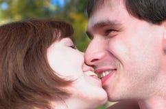 Lyckligt kyssa kopplar ihop i autunmskogen fotografering för bildbyråer