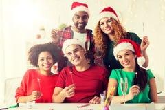 Lyckligt lag som firar jul på kontorspartiet royaltyfri bild