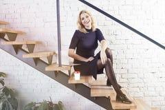 Lyckligt le affärskvinnasammanträde på trappa i modernt kontor och att arbeta på bärbara datorn och ha kaffe, solskendagsljus royaltyfria bilder