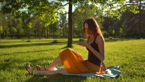 Lyckligt le attraktivt kvinnasammanträde på grönt gräs och har konversation via den digitala smartphoneapparaten lager videofilmer