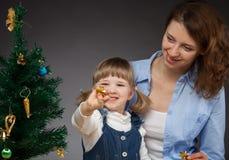 Lyckligt le behandla som ett barn flickan, och hennes mamma dekorerar julen tr Arkivfoton