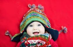 Lyckligt le behandla som ett barn i en rolig färgrik hatt och halsduk fotografering för bildbyråer
