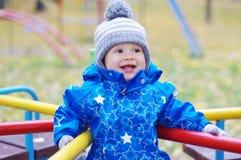 Lyckligt le behandla som ett barn pojken utomhus i höst på lekplats Fotografering för Bildbyråer