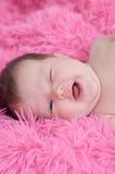 Lyckligt le behandla som ett barn ståenden som är nyfödd behandla som ett barn flickan som ligger på rosa bakgrund Arkivfoton