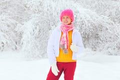 Lyckligt le bära för kvinna färgrik kläder i snöig vinter Arkivbild